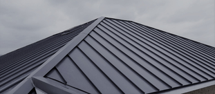 This is a picture of a house that has a newly installed black standing seam metal roof.  The sky in the background is cloudy.  Metal roofs are known to withstand harsh weather conditions.