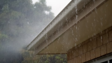 This is a picture of a small section of an eavestrough.  The eavestrough is overflowing with water.  There is a rainstorm in the background.  Eavestrough repair and installation by Belleville roofing.