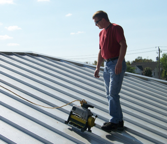 Picture of a roofer standing on a grey and black standing seam metal roof.  He is working on installing the roof.  There is a roof seamer on the roof.  This type of machine is used to install standing seam metal roofs.